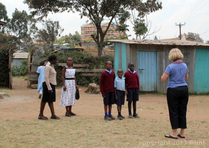 the slum schoolyard in the shadow of a middle class high rise.